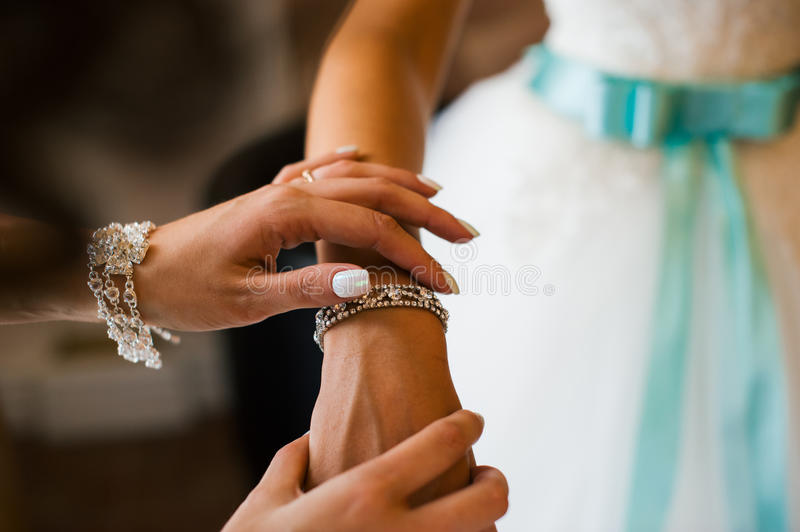 Bridesmaid helps to tie a bow on a festive white dress of the bride on the wedding day. Girl straightens his hands bracelet jewelry on the bride`s wrist stock photography