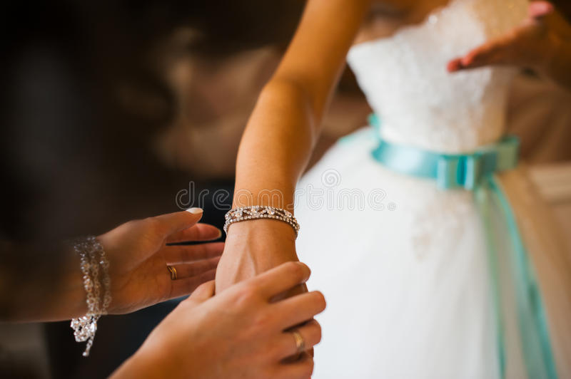 Bridesmaid helps to tie a bow on a festive white dress of the bride on the wedding day. Girl straightens his hands bracelet jewelry on the bride`s wrist stock photos