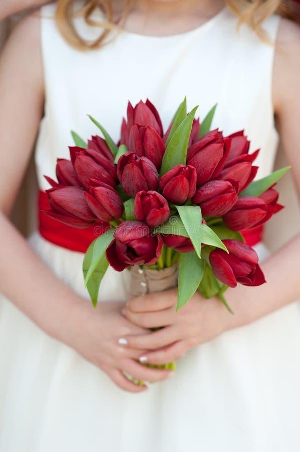 Red tulip wedding bouquet. Bridesmaid holding red tulip wedding bouquet stock photos