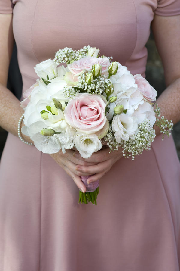 Bridesmaid holding wedding bouquet of pink flowers royalty free stock photography