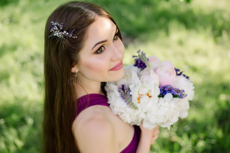 Bridesmaid with luxurious colorful wedding bouquet of peonies and other flowers standing at the ceremony in purple. Bridesmaid with luxurious colorful wedding stock photography