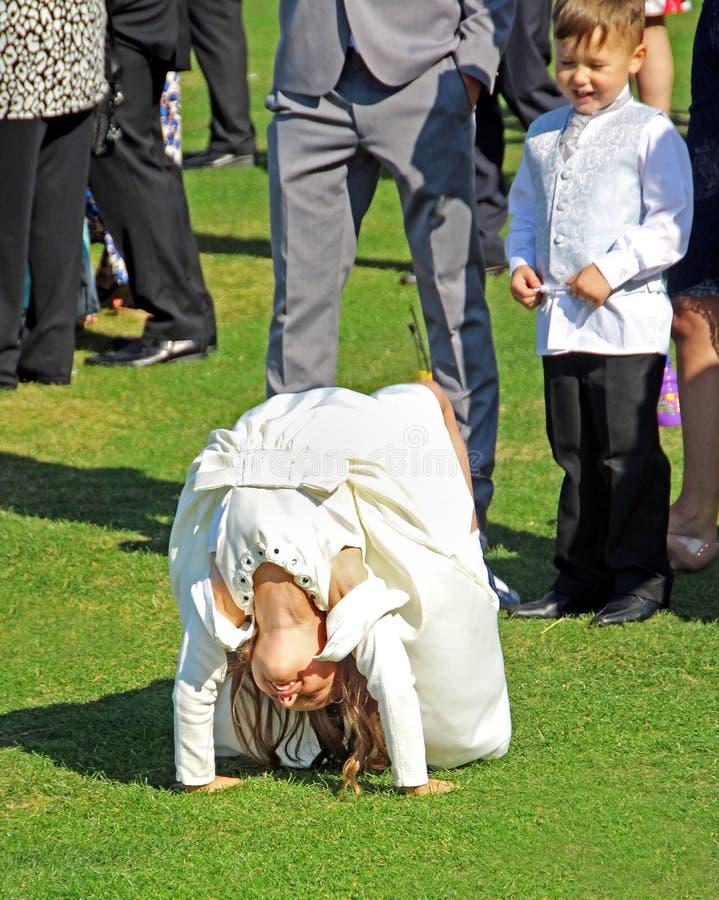 Bridesmaid performing acrobatic stunts at wedding reception. Photo of a young bridesmaid showing off her talent by performing acrobatic stunts in front of a stock image