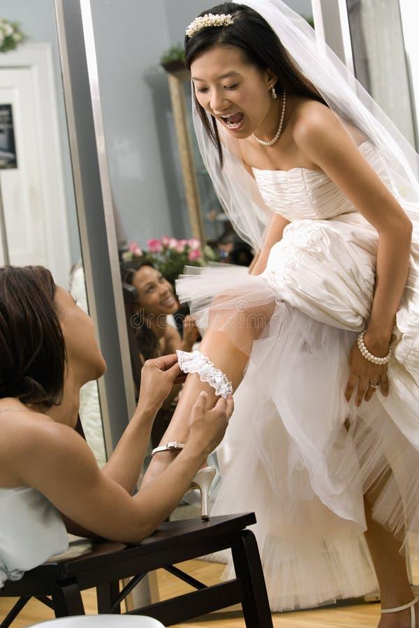 Bridesmaid placing garter. African-American bridesmaid placing garter on Asian bride's leg royalty free stock photos
