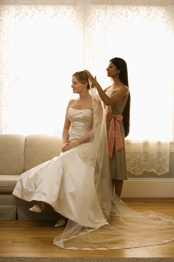 Bridesmaid placing veil. Indian bridesmaid placing veil on Caucasian bride stock images