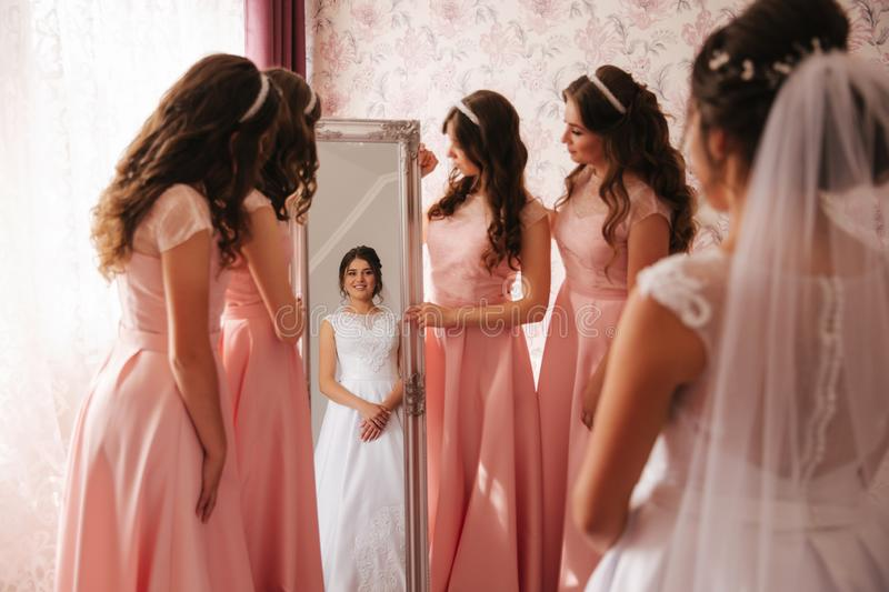 Bridesmaid standing by the mirror and help bride look at yourself. Big mirror at home. Happy girl`s in same dress stock photo