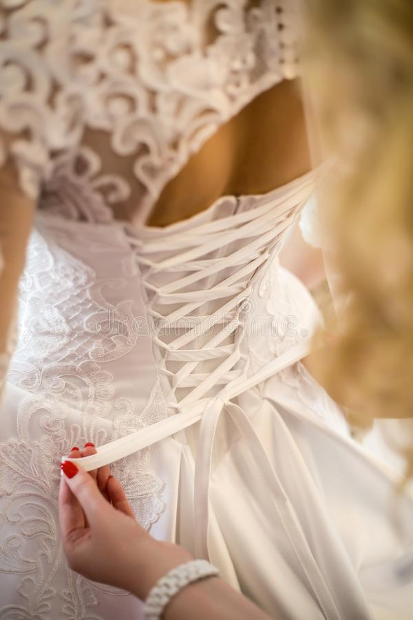 Bridesmaid tying wedding dress. lace wedding dress. charges of the bride.  stock images