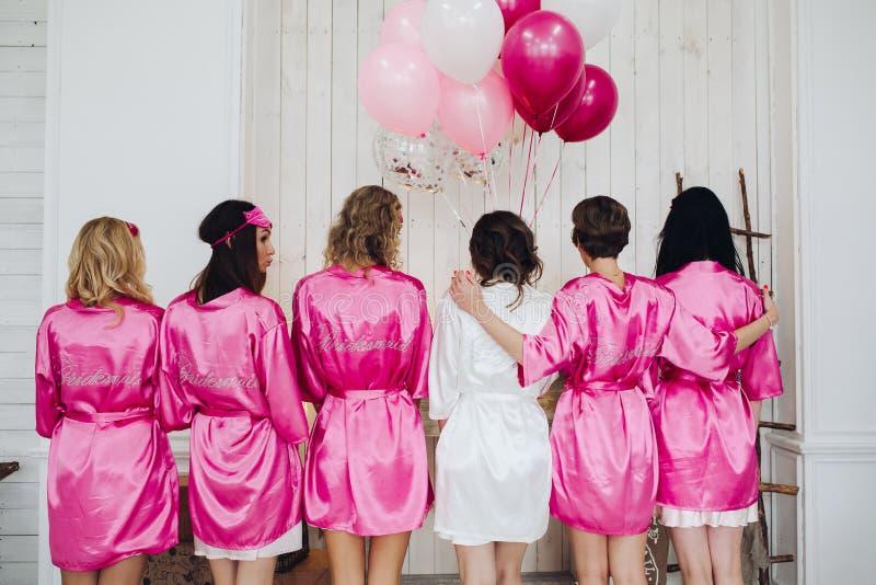 """Bridesmaids в розовых робах шелка со словом """"bridesmaid """"на bac стоковые изображения"""