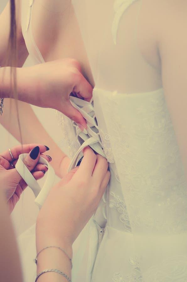 Bridesmaids помогают зашнуровать вверх оплетку на платье тонизировать instagram стиля стоковое изображение rf