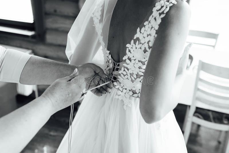 Bridesmaids help to wear a wedding dress royalty free stock photos