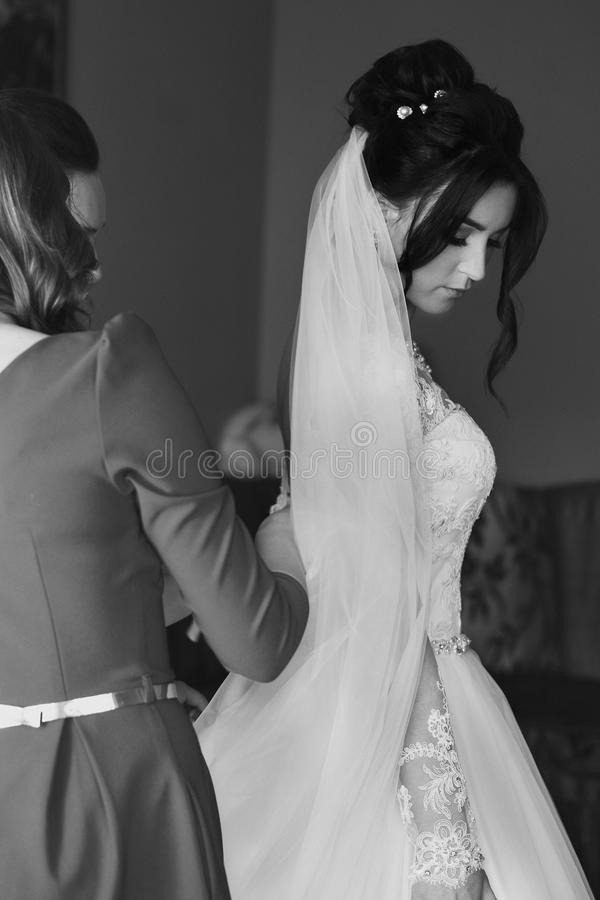 Bridesmaids helping beautiful bride to put on dress lace cl stock images