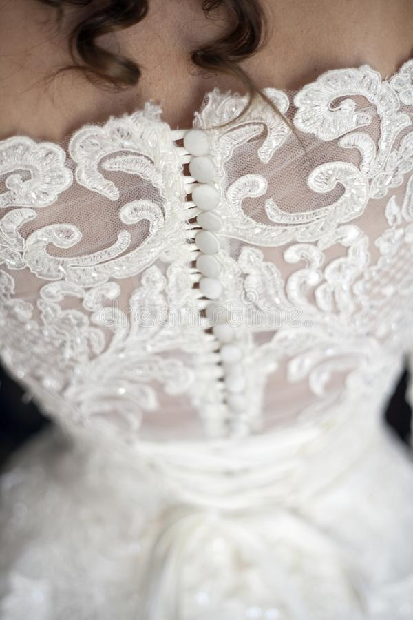 Bride putting on her white wedding dress royalty free stock photo