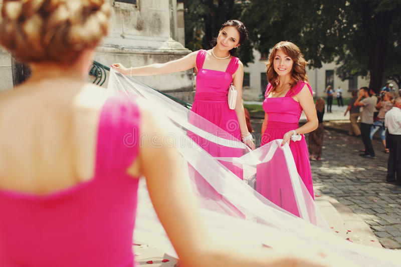 Bridesmaids hold a big white cloth standing in the front of the stock images