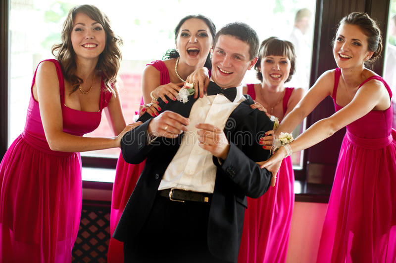 Bridesmaids hold groom's shoulder and smile royalty free stock photos