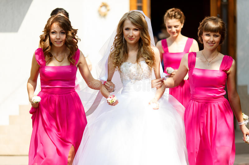 Bridesmaids in pink dresses hold bride's arms walking out of the stock photos