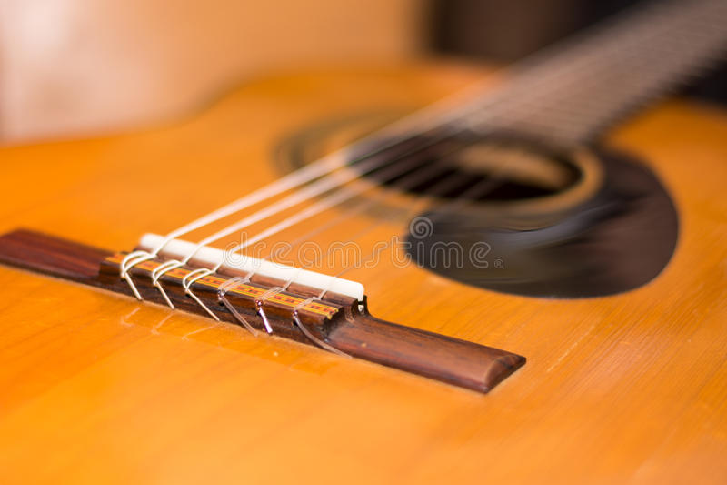 Bridge on the accoustic guitar in the focus.  stock photography