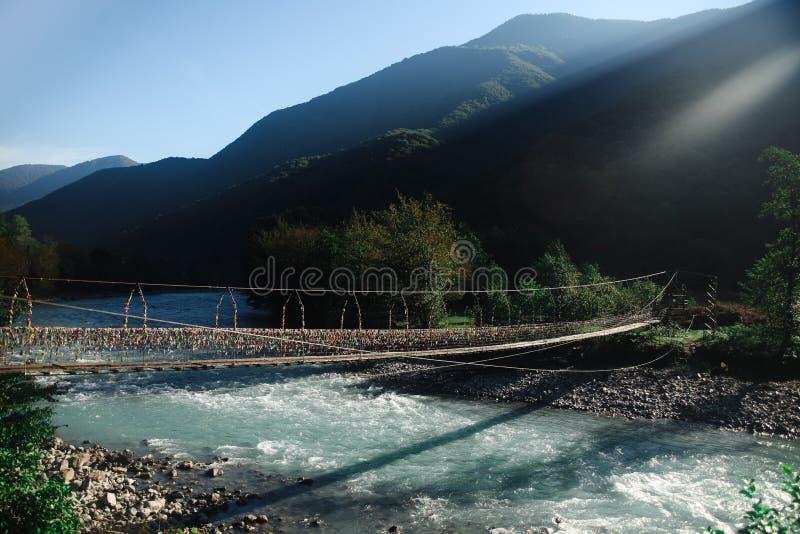 Bridge across mountain river stock photo
