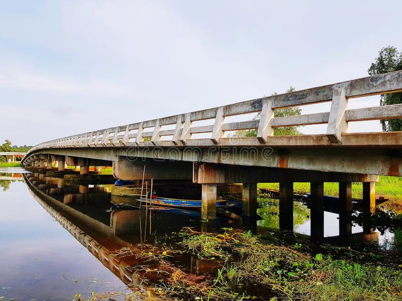 Bridge across river at countryside. Rural, architecture, landmark, outdoor, nature, concrete, thailand, wetland, canal, riverside, river-view, environment royalty free stock image