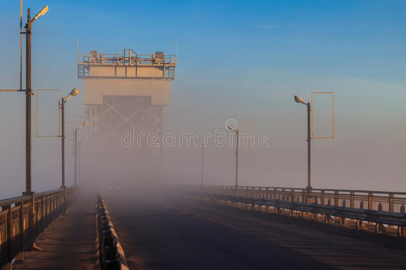 Bridge across river Dnieper in fog in the morning at autumn. Kremenchug, Ukraine. Bridge across the river Dnieper in fog in the morning at autumn. Kremenchug royalty free stock photography