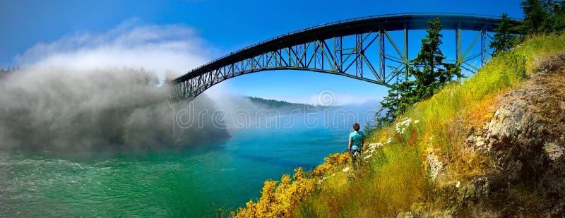 Bridge across water in foggy morning. stock photo
