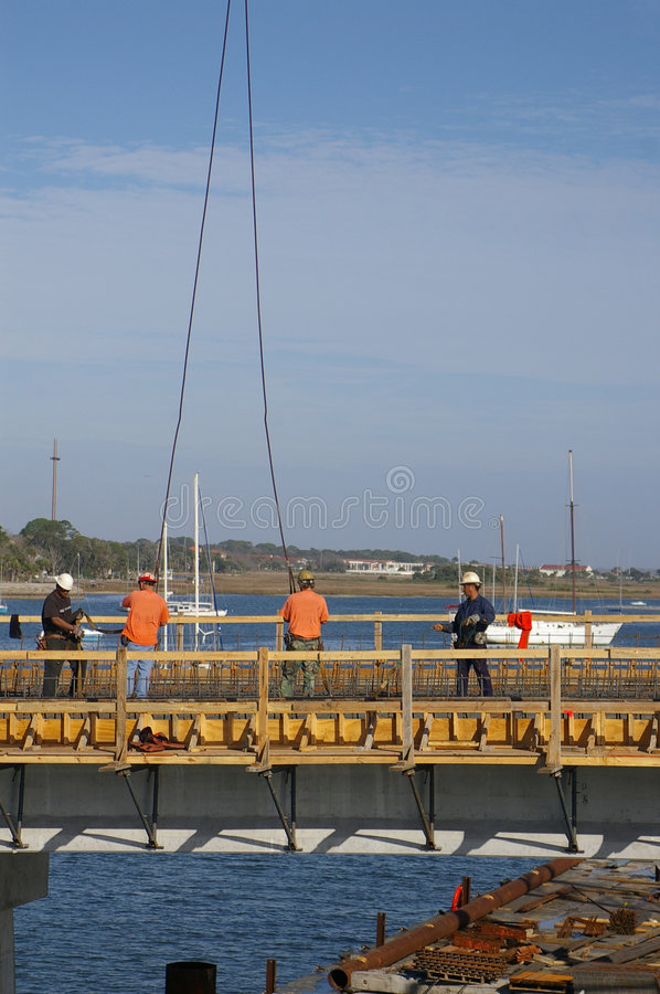 Bridge builders over water royalty free stock photography