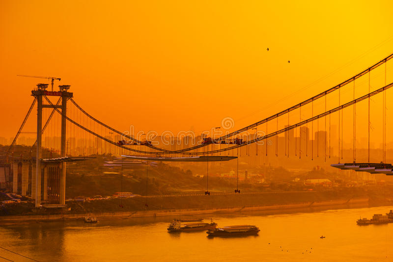 Bridge construction and pigeon. This is a new bridge which was building on the Yangtze River when the sun was down. The pigeons are flying in the golden sky stock photography