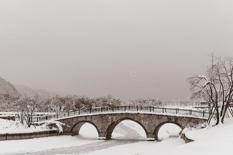 Bridge covered snow with frozen river royalty free stock photo