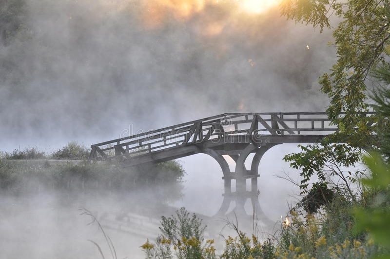 Bridge in Fog. A bridge spans a river, sitting quietly in the morning fog right as the sun begins to shine through the treetops royalty free stock photography