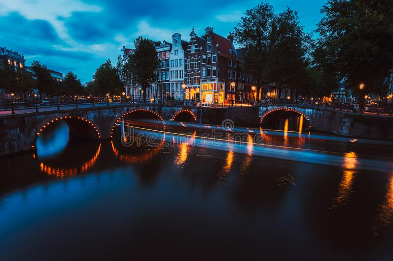 Bridge illumination and boat light trails in evening Amsterdam with reflection in Herengracht canal. Typical dutch. Houses in dusk light, Holland, Netherlands royalty free stock images