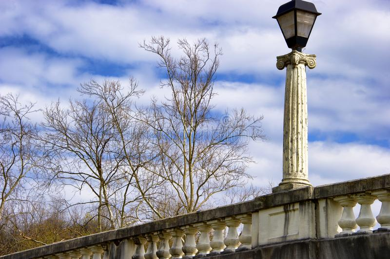 Bridge Lamp Post and cloudy skies. Background image of a bridge lamp post, tree branches and cloudy skies stock image