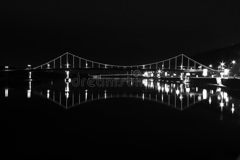A bridge with lanterns in the water at night stock photography