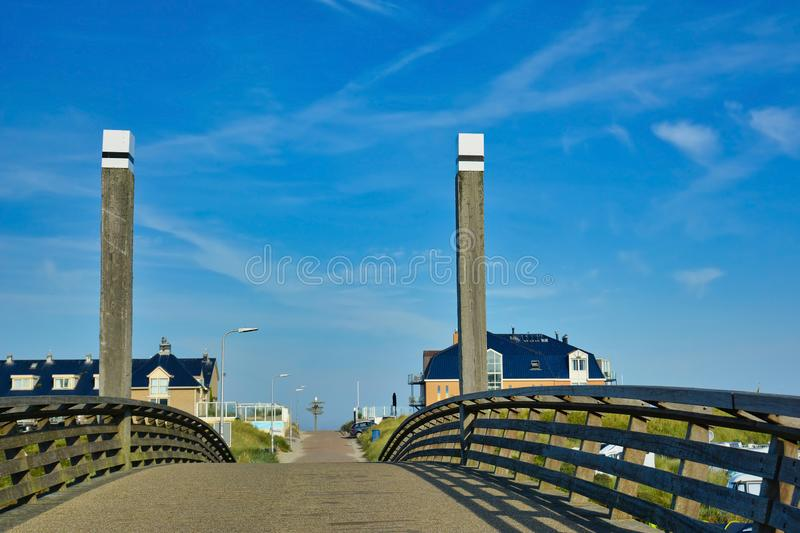 Bridge leading to beach `Paal 20` in city De Koog on dutch island Texel on a summer day with blue sky stock images