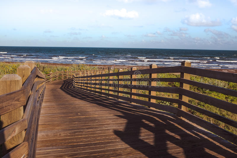 Bridge leading to the ocean. Wooden bridge or pathway leading towards the ocean stock images