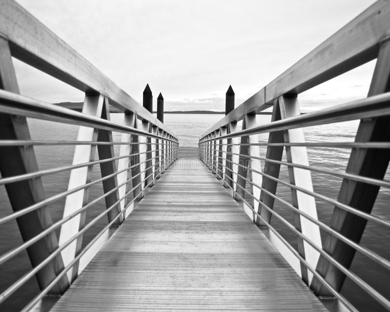 A bridge leads to a floating dock. The leading lines vanish into a floating dock formed by a bridge in Bellingham Bay stock photos