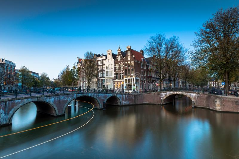 A bridge with lights and boat streaks over the Keizersgracht Canal. A bridge with lights over the Keizersgracht Canal during the blue hour with streaks of boat royalty free stock photography