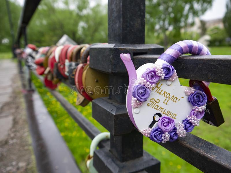 Bridge with many locks with the names of the newlyweds as a sign of love. Hard padlocks with keys thrown into the river are a stock images