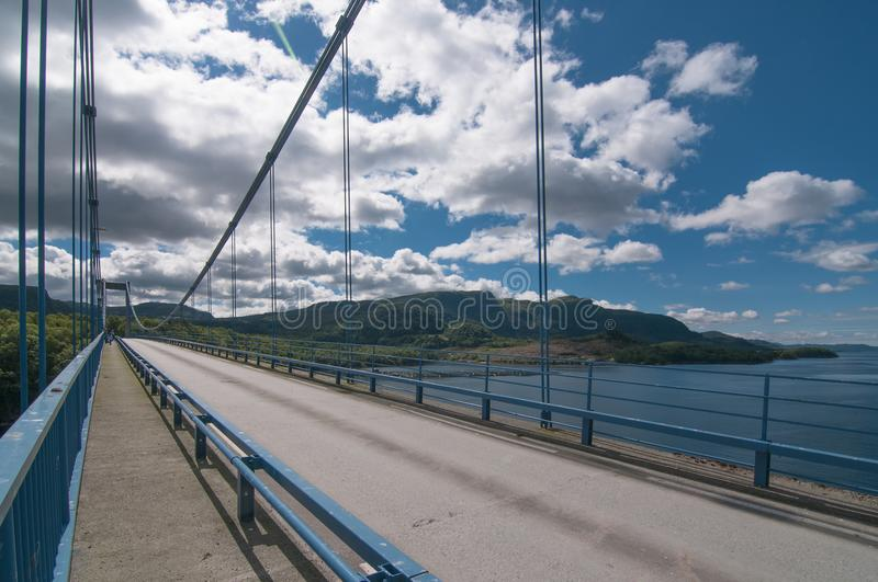 a bridge over the a channel over background with hills and clouds in a sunny day royalty free stock photography