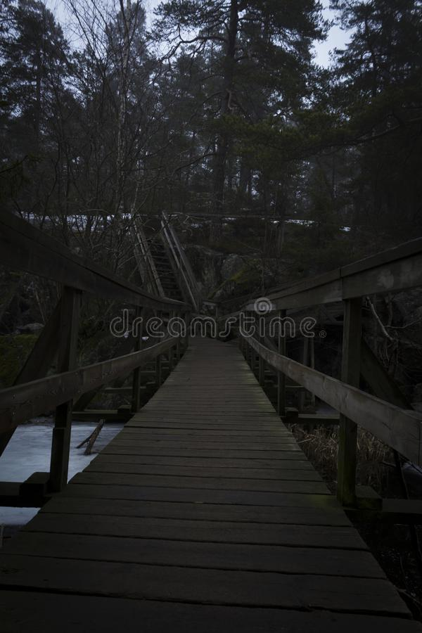 Bridge over a lake and stairway up a mountain, to a forest. Nature reserve in Sweden stock photography
