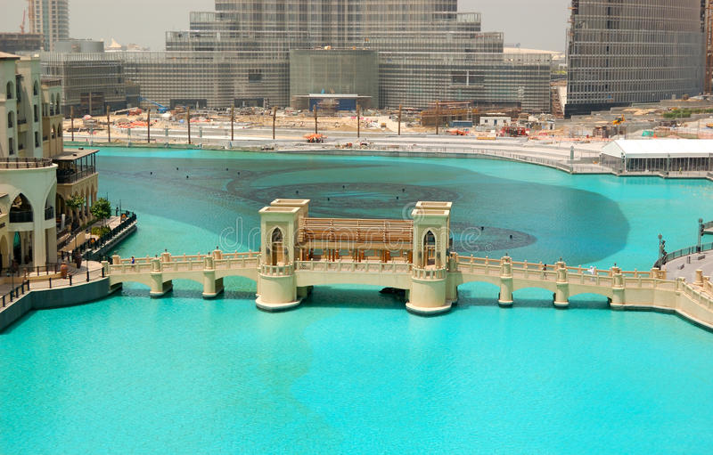 The bridge over man-made lake in Dubai downton. DUBAI - AUGUST 27: The bridge over man-made lake in Dubai downtown. It is located in Burj Khalifa complex near royalty free stock photos