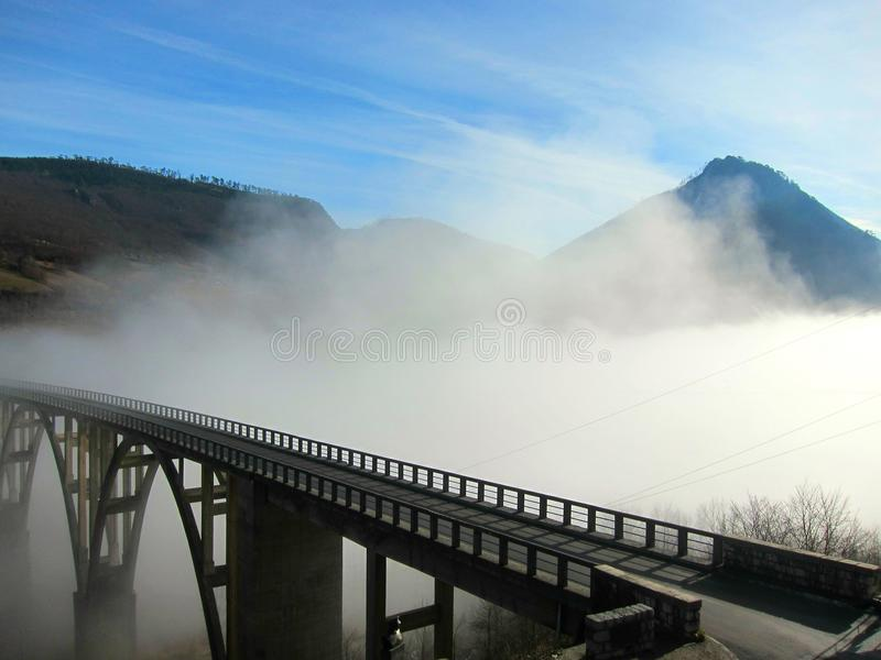 Bridge over a mountain river in the cloud stock image