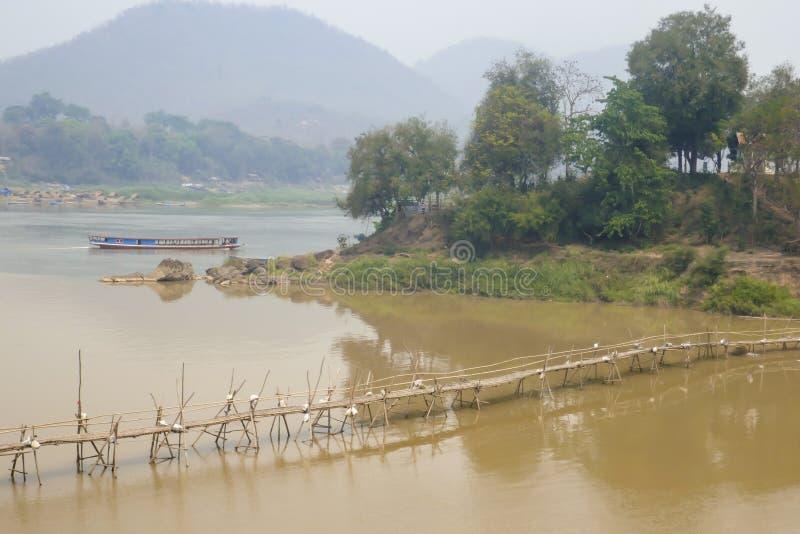 Bridge over Nam Khan River in Luang Prabang Laos. Bamboo bridge build annually at low water in dry season over Nam Khan River at confluence of Mekong River in stock photos