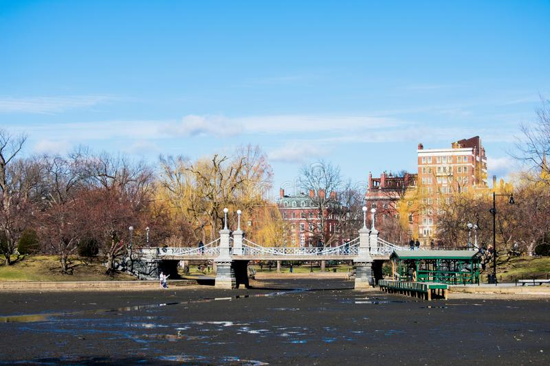 A bridge over no water in a park. With a blue sky, grass, and pretty trees stock image