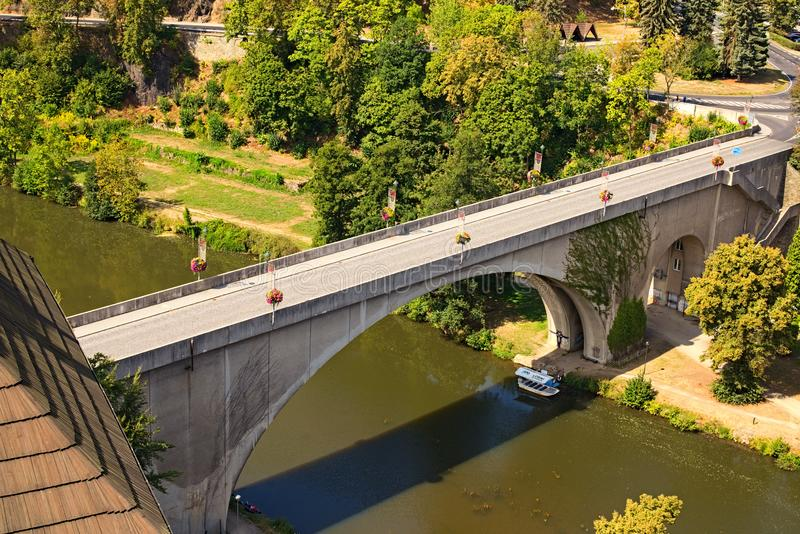Bridge over Ohre River to medieval part of Loket town. Little boat for tourist trips under the bridge. stock photography