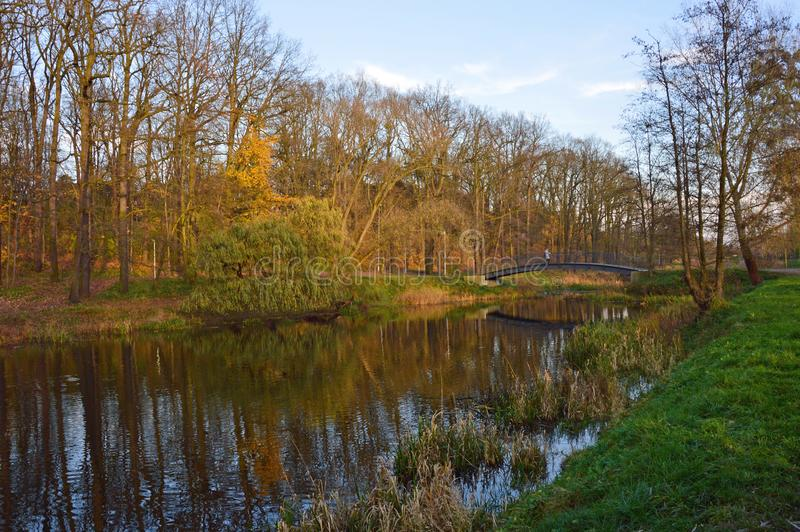 Bridge over the old river in the park during last sunny days of fall. stock photos