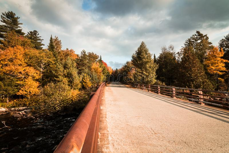 Bridge surrounded by brilliant fall foliage in upstate NY royalty free stock photos