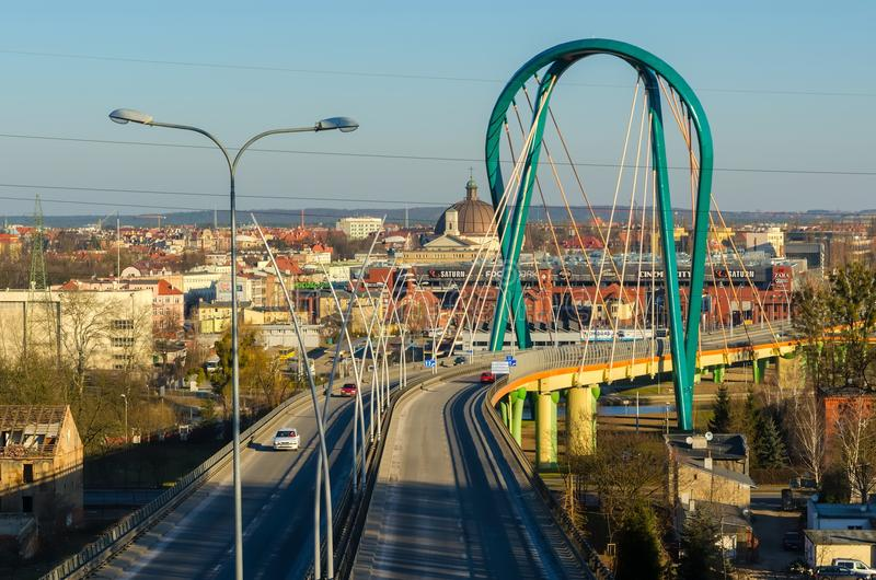 Bridge over a river. Bydgoszcz, Poland. BYDGOSZCZ, POLAND - FEBRUARY 17, 2015: Cable stayed bridge over Brda river with shopping centre and church in the royalty free stock photography