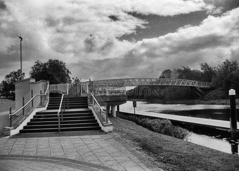 The bridge over a river on a cloudy day. This black and white photo was taken with a pinhole film camera, which corresponds to the camera characteristic royalty free stock images