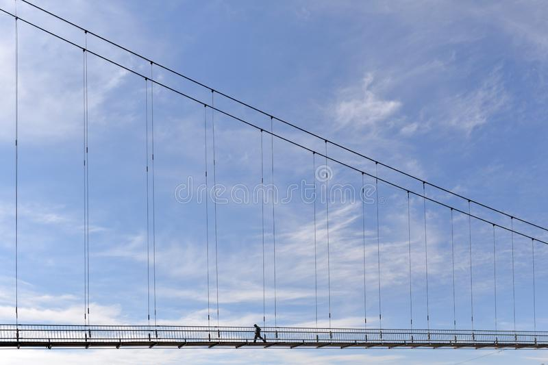 A bridge over a river with a man walking along it against a blue sky. royalty free stock photos