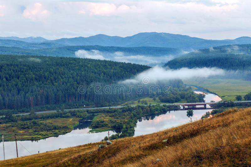 Bridge over river. The Ural Mountains. Bridge over the river in a picturesque valley. Ural mountains. Bashkortostan stock images