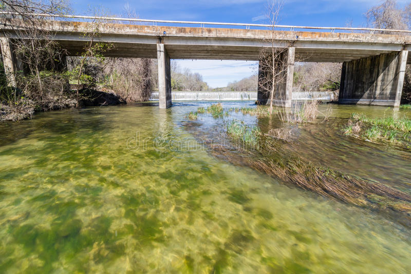 Bridge Over the San Gabriel River. Waterfall on the San Gabriel River in Georgetown Texas taken in the beginning of Spring, grass turning green. Water running royalty free stock photo