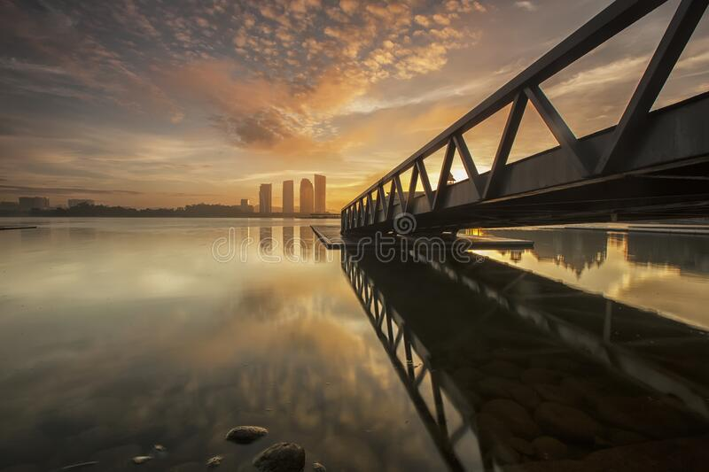 Bridge over sea with city skyline at sunset royalty free stock photography